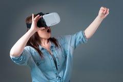 使用VR耳机的情感少妇和体验在灰色背景的虚拟现实 免版税图库摄影