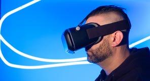 使用VR虚拟现实耳机未来派网际空间的人 免版税库存照片