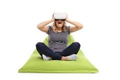 使用VR风镜的妇女供以座位在装豆子小布袋 免版税库存照片