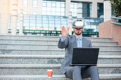 使用VR风镜的成功的年轻商人和做手势,运作在办公楼前面的一台膝上型计算机 图库摄影