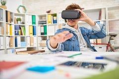 使用VR玻璃的微笑的年轻人在工作 免版税库存图片