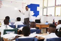 使用whiteboard的老师在教训期间在一所小学 库存图片