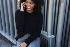 使用wifi,户外迷人的快乐的非裔美国人的妇女消费业余时间 免版税库存图片