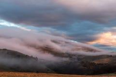 使盖有些山和树模糊,用温暖的日落颜色 免版税图库摄影