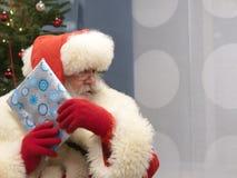 使礼物窘迫不安的真正的圣诞老人 库存图片