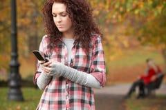 使移动电话的购买权沮丧的女孩少年 免版税图库摄影