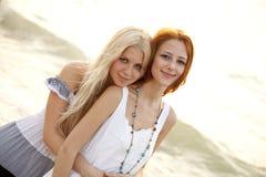 使美丽的女朋友靠岸二个年轻人 免版税库存图片