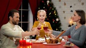 使自Xmas前夕的父母酒,孩子饮用的汁液,幸福家庭庆祝叮当响 图库摄影