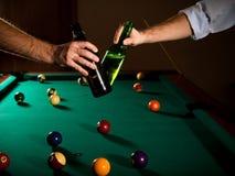 使落袋撞球叮当响的啤酒瓶 免版税库存图片