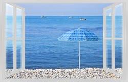 使蓝色伞反对从窗口的海视图- conce靠岸 库存照片