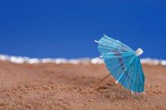 使蓝色遮阳伞沙子海运天空靠岸 库存照片