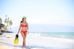 使走由海洋的妇女靠岸-比基尼泳装和废气管 免版税库存图片