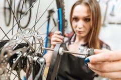 使轮子恢复原状的女性技术员在车间 免版税库存图片