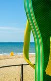 使阵雨靠岸以在海滩散步的一块挡水板的形式在Th 库存照片