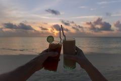 使鸡尾酒叮当响的两只手在海滩的日落期间 热带海岛假期 快乐时光 库存图片