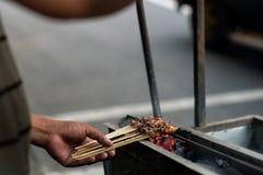 使鸡的过程satay由摊贩通过使用木炭火 库存照片