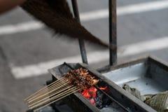 使鸡的过程satay由摊贩通过使用木炭火 库存图片