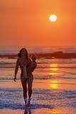 使系列四沙子热带假期空白年轻人靠岸 有儿童步行的母亲在日落海滩 免版税库存图片