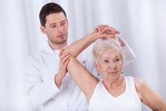 使年长妇女恢复原状的生理治疗师 免版税库存图片