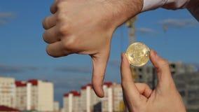 使bitcoin和拇指的男性手保持向下,落,减少,特写镜头, bitcoin,拇指下来 股票视频