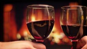 使glasseswith红酒叮当响的两只手特写镜头射击庆祝与舒适温暖的壁炉的夜日期在 影视素材