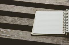 例证百合红色样式葡萄酒 在木桌上的空白的笔记本页 与拷贝空间的顶视图 免版税图库摄影