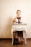例证百合红色样式葡萄酒 坐在减速火箭的书桌的赤足女孩 图库摄影