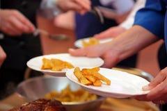 侍者供食烤肉和被烘烤的土豆在党或我们 免版税库存图片