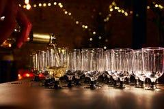 侍者倒在玻璃的白葡萄酒在假日招待会桌上 免版税库存图片