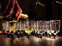 侍者倒在玻璃的酒在假日招待会桌上 免版税库存图片