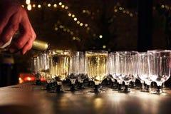 侍者倒在玻璃的酒在假日招待会桌上 免版税图库摄影