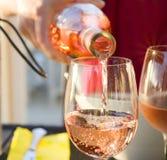 侍者倒桃红色法国葡萄酒入玻璃火花 库存照片