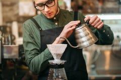 侍者倾吐在咖啡罐的热的煮沸的水 库存图片