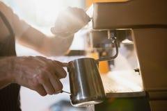 侍者倾吐的牛奶的中间部分在水罐的从咖啡机器 免版税库存照片