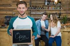 侍者在背景中的拿着有开放标志的黑板和顾客 免版税库存照片