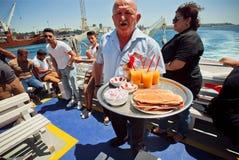 侍者在船上横跨Bosphorus的轮渡 免版税库存照片