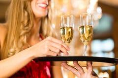 侍者在餐馆服务在盘子的香槟玻璃 免版税库存照片
