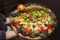 侍者拿着与一条大开胃被烘烤的鱼的一个大板条 免版税图库摄影