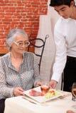 年轻侍者服务午餐 免版税库存照片