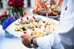侍者服务新鲜的海鲜盛肉盘 免版税库存图片