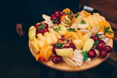 侍者服务的葡萄,在一块白色板材的橙色香蕉梨热带水果分类在酒精饮料的餐馆 库存图片