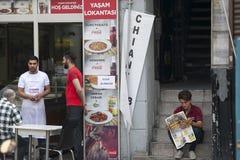 侍者服务街道咖啡馆的访客 读报纸的一个年轻人,坐步 免版税库存图片