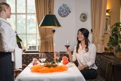 侍者服务酒在一家美好的餐馆 免版税库存照片