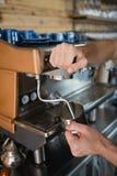 侍者特写镜头递在水罐的倾吐的牛奶从咖啡机器 免版税库存照片
