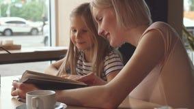 侍者给一些饮料小女孩在咖啡馆 免版税库存照片