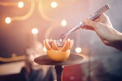 侍者调直煤炭水烟筒shisha用在橙色果子的烟草在夜总会或酒吧 免版税库存照片