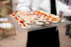 侍者运载的开胃菜和手抓食物 免版税图库摄影