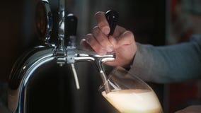 侍酒者使用啤酒轻拍并且倒桶装啤酒对在慢动作,泡沫似的金黄麦子啤酒的玻璃倾吐对啤酒 股票录像