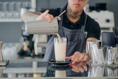 侍酒者倾吐在玻璃的牛奶鸡尾酒在有酒吧柜台的当代设计样式餐馆里面 免版税库存照片