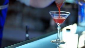 侍酒者倾吐的混杂的利口酒到准备的玻璃里通过鸡尾酒过滤器 库存照片